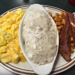 Biscuit and gravy with eggs bacon and potatoes