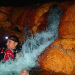 Our guide Andy dragging the tube through waterfalls in the cave