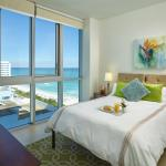 Bedroom with King bed and floor-to-ceiling windows in Deluxe Ocean View apartment suite.