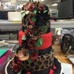 Hand painted hand made animal print flowers decorate this 3 tier fondant cake
