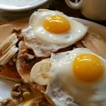 The sunny side eggs over three Multi Grain Pancakes with walnuts and sliced bananas, large bowl
