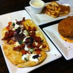 Mediterrean flatbread with goat cheese quesadilla and fried stuffed potatoes in background
