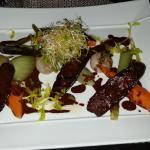 photo d'une entrée du menu. Figatelli grillée sauce cacao  petits légumes.