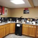Breakfast room had OJ, coffee, milk, waffles, cereal, bagels, mini muffins, powdered doughnuts,