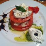 buffalo mozzarella and beef tomato starter with pesto, balsamic glaze and ricotta cheese (I thin