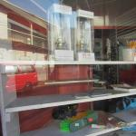 Things for sale in the front window - Kerosene lamps, plastic sandals, broom, pencils & books!