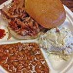 large pulled pork sandwich with bbq beans and potato salad