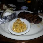 Steak, baked potato and corn.