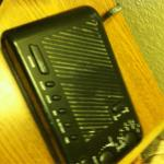 Dirty clock radio beside the bed.