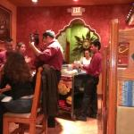 The waiters singing Las Mañanitas for a customer's birthday while another makes guacamole tables
