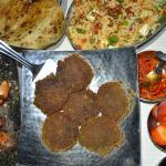 Clockwise l-r naan, briyani, chutney, salad, paneer dish, kabab dish, tikka dish