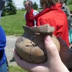 Tour leader showing a pot he dug up on a dig near this part of the tour.