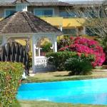 Glorieta y hermosa piscina en el jardín.