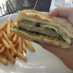 Burger with lettuce and pesto spread with french fries