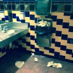 Full trash can and dirty paper towels on the floor in the men 's restroom on 4/10/15.