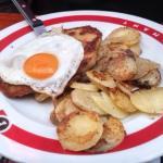 carne de cerdo empanada, con patatas con trozos de bacon y cebolla, y huevo frito