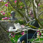A performance artist in the garden writing out 100 great classics is copying Orlando