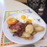 Fruit Pancakes with eggs over easy, bacon, sausage and toast