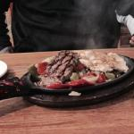 Sizzling steak and chicken fajitas.