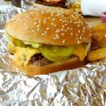 Cheeseburger with grilled onions, pickles, lettuce, mustard, and ketchup.
