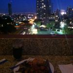 Eating our BBQ food on the rooftop overlooking the city lights
