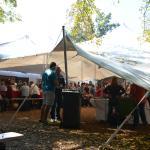 Carpa con puestos de comida, venta de productos artesanos y música en directo