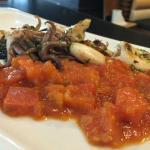 Txipirones plantxa en su tinta con tomate para menú del diá