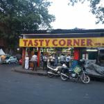 Shop at the street corner,with people eating,standing in the front of it