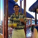 A born entertainer, Ismael carrying numerous drinks. He RUNS downstairs with a drink on his head