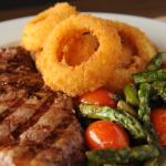 Mouth-watering steaks served with onion rings
