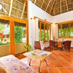 Upper bungalows feature large windows and palapa roofs.