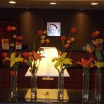 The front desk is conveniently located just behind the floral arrangement.