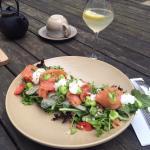 Прекрасный салат из свежих листьев салата, тонко нарезанной рыбы, соуса и зерен перловки и гречк