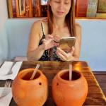 Thai iced tea served in earthenware mugs.