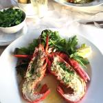 Whole Canadian Lobster in Garlic Butter with dressed leaves.