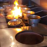 Curries cooking on the stove next to the tandoor oven