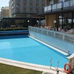 Grande piscina con idromassaggio, geysere e lettini su prato all'inglese