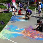Talented artists making chalk drawings on the sidewalk