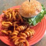 Blackened crab cake sandwich with curly fries.