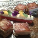 El cochinillo crujiente con membrillo de tomate, flores, albahaca y ajos