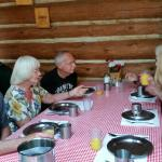 Sitting at the long tables at the original logging camp