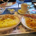 Breakfast consisting of cheese omelet, home fries, crispy bacon and pancakes.