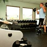 Gym with cardio machines, weight machines, free weights, and group fitness