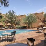 Bereich des Pools mit angrenzenden Liegeflächen und eingeschossigen Gebäuden mit Zimmern und Sui