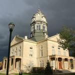 Madison County, Iowa Courthouse in bright sun with dark clouds behind it