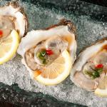 Oysters in a half shell with ponzu sauce.