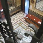 View of the huge hall with the original tiles, through the wrought iron ballustrades.