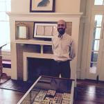 Tour guide describing Fitzgerald stamp collection in glass case