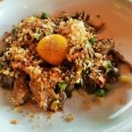 Mushrooms (hen-of-the-wood), with an egg yolk and ham crumbs on top of chicken confit, peas, cor