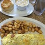 Meat lovers omelet, fried potatoes and a biscuit with gravy.